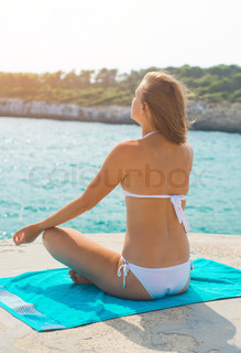 Young woman practising yoga near the sea.