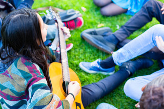 Friends singing songs in park having fun together