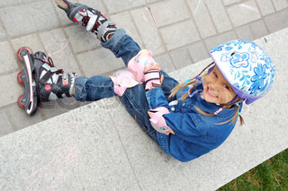 child with rollerskates and protective helmet and knee and elbow and palm pads