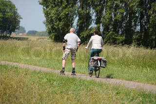 The man is on skates with protected elbows and knees and the woman with her bike are in the park in the summer in Holland.