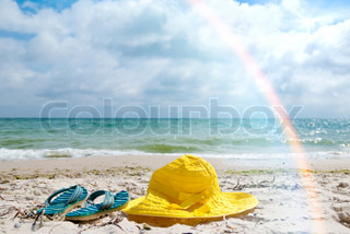 Yellow hat and blue flip-flop on a beach
