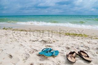 zwei Sandalen am Strand in der Nähe von Meer