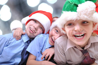 group of happy kids with Santa hats