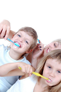 People  cleaning  teeth over white background. Mother is helping her son to do it well.Shallow depth of field. The focus is on the boy's face.