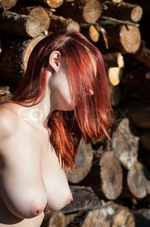 nude woman and pile of wooden logs