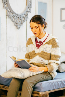 Happy woman relaxing at home and reading a book