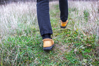Person wearing walking shoes takes a step on a mountain hiking path, closeup photo.