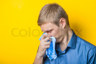 Young man close-up in a blue shirt on a yellow background, cold, cold, blowing his nose in the handkerchief. Mimicry. Gesture. photo Shoot