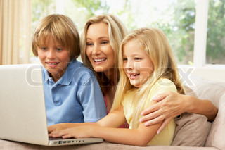 Mother And Children Using Laptop At Home