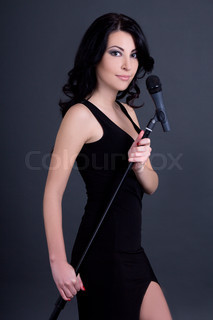 young beautiful woman singer with microphone over grey