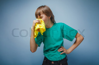 boy teenager European appearance brown hair blowing his nose in
