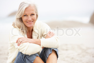 Senior Woman On Holiday Sitting On Winter Beach