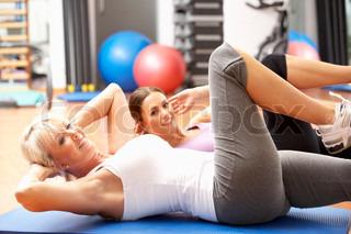 Kvinder Doing Strækker Øvelser i gym