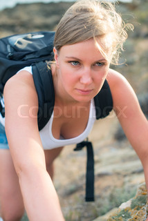 Pretty woman with backpack hiking in the mountains.