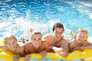 Young family having fun together in pool