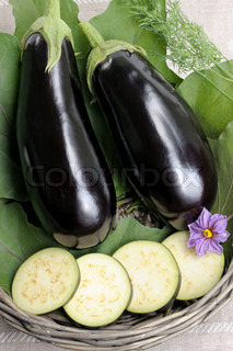 Two eggplants of black colour in a basket on leaves and the cut slices