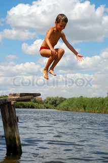7 year old boy jumping into the water.