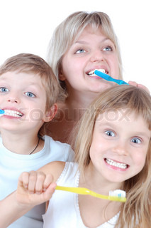 family with two children  cleaning  teeth over white background