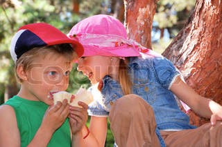 two kids in the park eating ice-cream