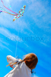 child flying a kite in the bright blue sky