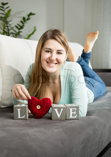 happy woman lying on sofa at room and holding word
