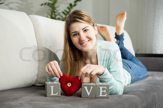smiling woman lying on sofa and making word