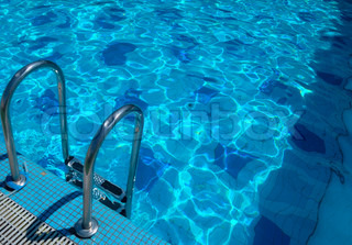 pattern of water of swimming pool with light in it and pool's stairway