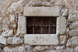 Secured window in weathered medieval stone house - Croatia.