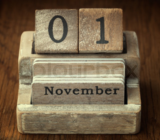 A very old wooden vintage calendar showing the date of 1st November on wood background