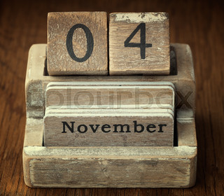 A very old wooden vintage calendar showing the date of 4th November on wood background