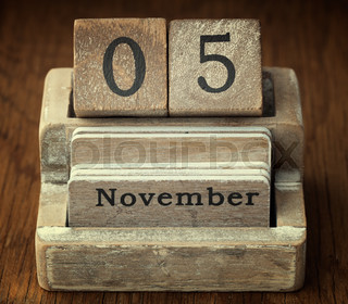 A very old wooden vintage calendar showing the date of 5th November on wood background
