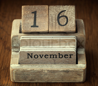 A very old wooden vintage calendar showing the date of 16th November on wood background