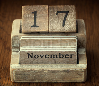 A very old wooden vintage calendar showing the date of 17th November on wood background