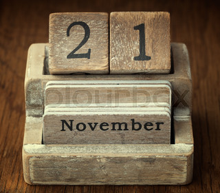 A very old wooden vintage calendar showing the date of 21st  November on wood background