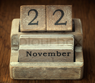 A very old wooden vintage calendar showing the date of 22nd  November on wood background