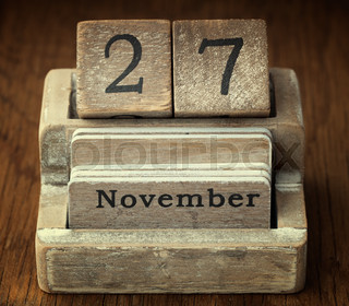 A very old wooden vintage calendar showing the date of 27th November on wood background