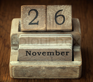 A very old wooden vintage calendar showing the date of 26th November on wood background