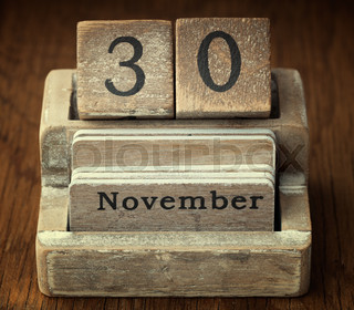 A very old wooden vintage calendar showing the date of 30th November on wood background