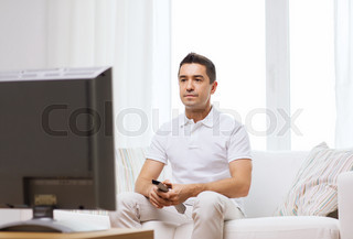 man with remote control watching tv
