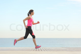Side view of a woman running on the beach