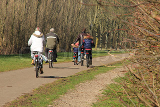 Couple, man and wife, and a father with his two sons cycling in the park in spring in Holland.