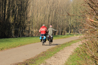 Couple, man and wife, cycling in the park in spring in Holland.
