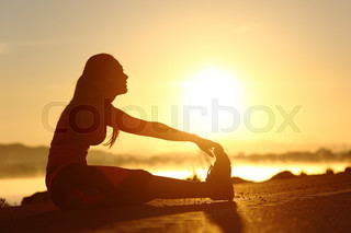 Silhouette of a fitness woman stretching at sunset