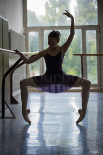 Young ballerina in training near the barre. Model standing on po