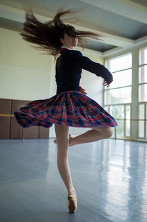 Long-haired ballerina spins in the dance moves on one leg to sta