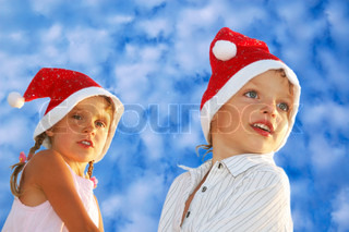 happy 5-6 year old boy and girl with Santa hats against the blue summer sky