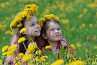 Brother and sister enjoy summer time in the dandelion meadow.