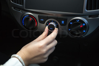 Woman turning on car air conditioning