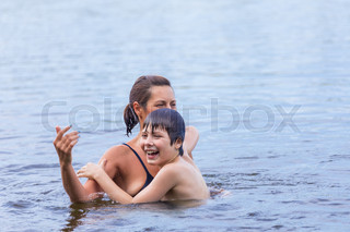 Mother and son swimming in the lake
