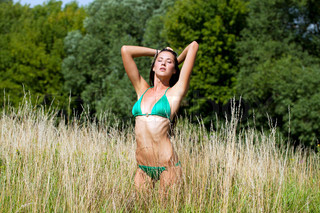 Beautiful model in a green bathing suit standing in the summer field